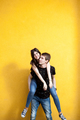 Cool young couple posing in fashion style on yellow wall