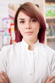 Young redhead pharmacist in front of her desk