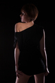 Attractive woman in black dress posing sexy on dark background