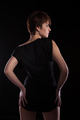 Hot woman in black dress posing sexy on dark background