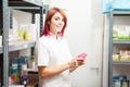 Pharmacist woman in the storage facility next to the shelfs