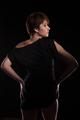 Beautiful woman in black dress posing sexy on dark background