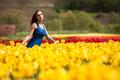 Sensual woman in flower field in sunny day