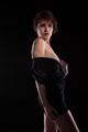 Model in black dress posing sexy on dark background