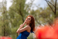 Sensual woman in red flower field in sunny day