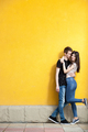 Happy couple posing in fashion style on yellow wall