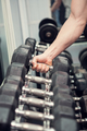 Powerlifter is picking a dumbbell