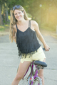Young woman, afternoon walk with her bicycle in the park