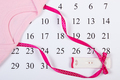 Pregnancy test with positive result wrapped ribbon and bodysuit for newborn on calendar