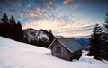 wooden alpine hut in winter mountains