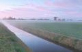 Dutch windmill by river in mist