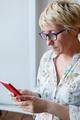 Mature female in glasses using smartphone