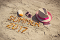 Inscription summer 2017, accessories for sunbathing and passport with currencies euro on sand