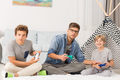 Boys playing video games with dad