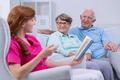 Caregiver reading to elderly couple