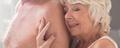 Senior woman embracing naked partner