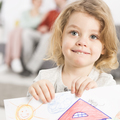 Smiling little girl holding drawing