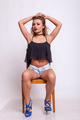 Gorgeous woman sitting on a chair in shorts jeans