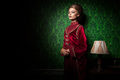 Rich woman dressed vintage clothes in retro interior