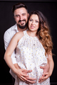 Inlove pregnant woman with her husband in studio photo