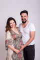 Pregnant smiling woman with her husband in studio photo