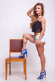 Beautiful woman in shorts jeans with her leg on chair