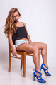 Sexy woman sitting on a chair in shorts jeans