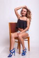 Beautiful woman sitting on a chair in shorts jeans