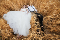 Bride and groom lying in wheat field
