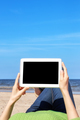Close up of female hands with tablet computer on a beach.