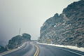 Retro color toned mountain road in fog.