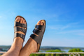 Male feet in leather slippers relaxing on balcony