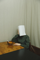 Vertical image of woman hiding behind piece paper