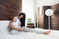 Happy mother with her cute child on the bed having a good time