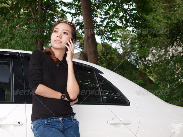 Young pretty Asian standing near car and calling by phone - Stock Photo - Images