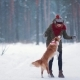 Young Woman Training Cute Dog in Winter