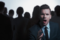 Businessman screaming in a crowd