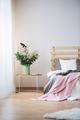 Bed and nightstand with flowers