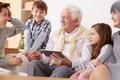 Grandchildren teaching grandpa to use a tablet