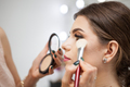 Close up of makeup trainer working with brush on a model face