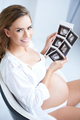 Pregnant woman holding her USG pictures