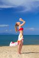 Joyful woman with arms raised at the beach