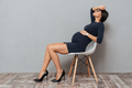 Bored pregnant business woman sitting over grey background.
