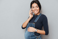 Smiling pregnant lady talking by phone.