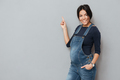 Happy pregnant lady standing over grey background pointing.