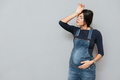 Tired pregnant lady standing over grey background