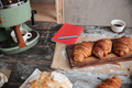 Pastries croissants on table near cup of coffee and notebook.