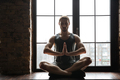Portrait of a healthy young sportsman meditating in lotus pose