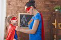 Girl and mom in Superhero costumes
