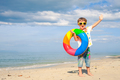Little boy with rubber ring standing on the beach